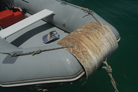 Top Photo:  Acrylic paint may help ease abrasions, but it also helps owners identify a dinghy and shields it from harmful UV rays. This Photo:  Even Captain Crunch cannot harm an old fender that has been split open and secured to the bow (or anywhere else around the dinghy).