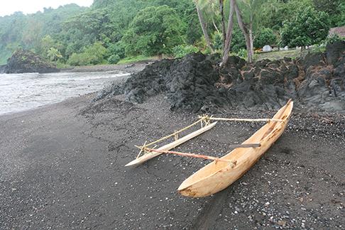 Newly built dugout canoe on black sand beach at Sasara Twin Waterfall Bay