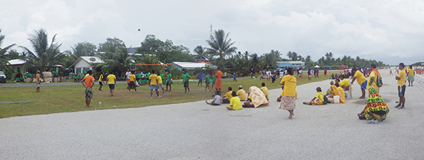 Spectators sit on the runway to watch competitive volleyball teams play on the grass nearby.