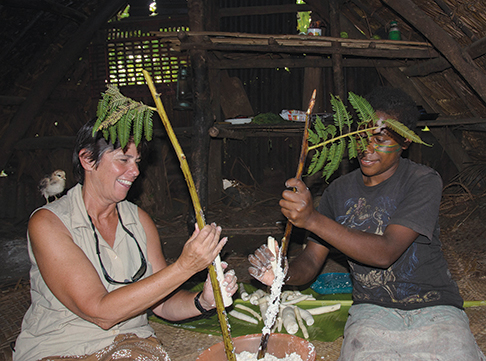 Grating manioc for laplap on black palm branches