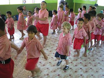Rufo, in sneakers, marching into Samoan kindergarten, Apia
