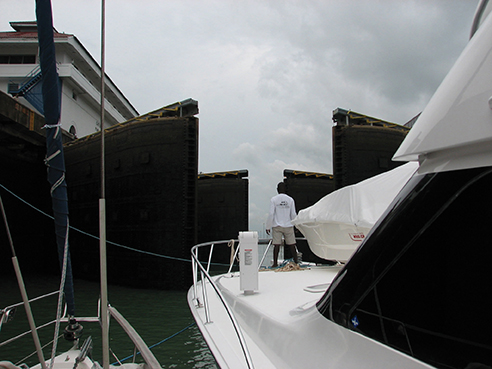 Two sailboats nested to a large sportfisher as the lock gates open
