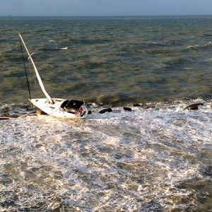 The sailboat French Kiss is battered on the Galveston, Texas, south jetty after Coast Guard Station Galveston and Air Station Houston crews respond Monday, Oct. 13, 2014. The aircrew hoisted the two men to safety and one man was treated for minor injures. (U.S. Coast Guard photo by Air Station Houston)