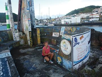 Amanda checks out what needs to be repainted on Mahina Tiare's logo on Horta marina's wall