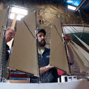 """Rockland, ME — March 30, 2017 -- Robert Guenther (left), volunteer, and Kirk Rouge, manager of the Sail, Power and Steam Museum in Rockland, look over the model of the """"Lavinia M. Snow"""", a three masted schooner built there in the late 1800s.  Guenther built the model ship for the museum's sign after the original one rotted. Linda Coan O'Kresik 