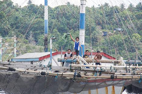 Fishermen aboard a big trimaran wave as we leave Jayapura