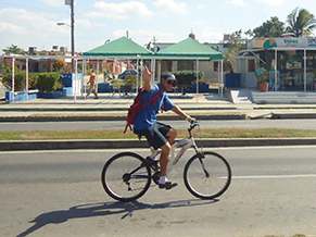 Pablo, captain of a Marlin tour boat, waves on his way to work in the Cienfuegos harbor. Bicycles are more common than cars for transportation.