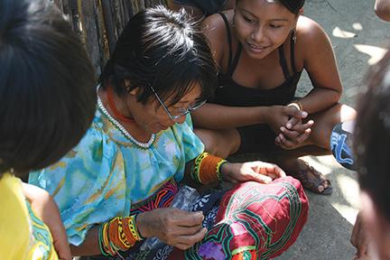 Kuna women testing donated eye glasses by sewing a mola - San Blas Island