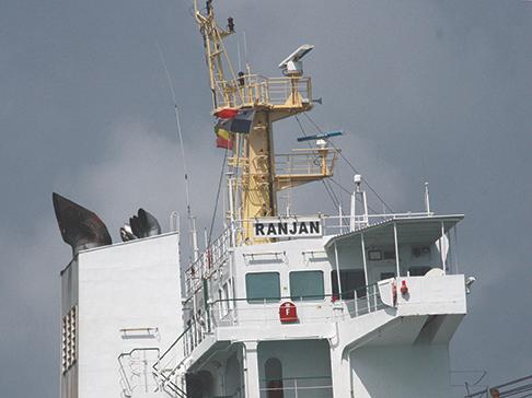 Cargo ship RanJan flying Panamanian courtesy flag, yellow quarantine flag, red hazardous cargo flag