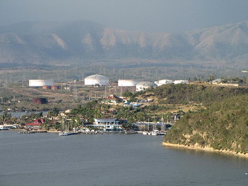A cruise terminal and hotel are in the works for Santiago Bay, shown here against a backdrop of fuel storage tanks and the Sierra Maestra mountains