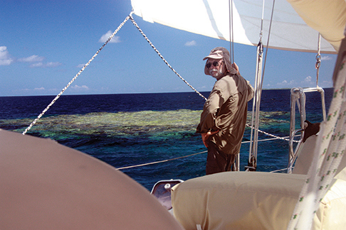 Dressed for the strong sun and sailing close by the reefs in deep water